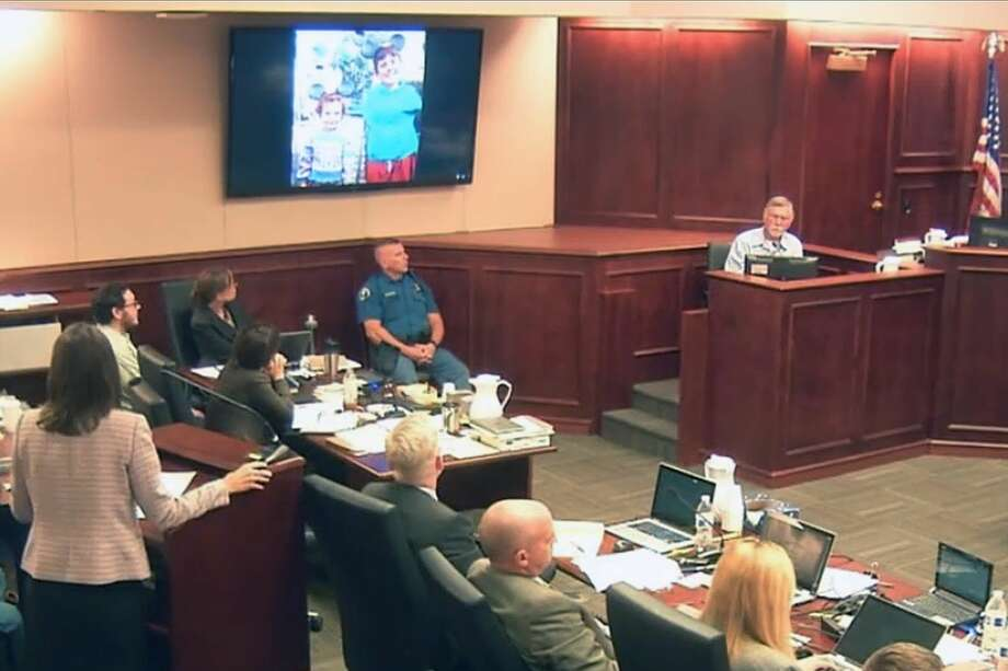 In this image made from Colorado Judicial Department video, defense attorney Tamara Brady, left, questions Robert Holmes, top right, the father of James Holmes, background left, during the sentencing phase of the Colorado theater shooting trial in Centennial, Colo., Tuesday. A family photo showing James Holmes and his younger sister, Chris, from a family trip to Disneyland is displayed on a monitor at center. Photo: Colorado Judicial Department Via AP, Pool / POOL Colorado Judicial Department
