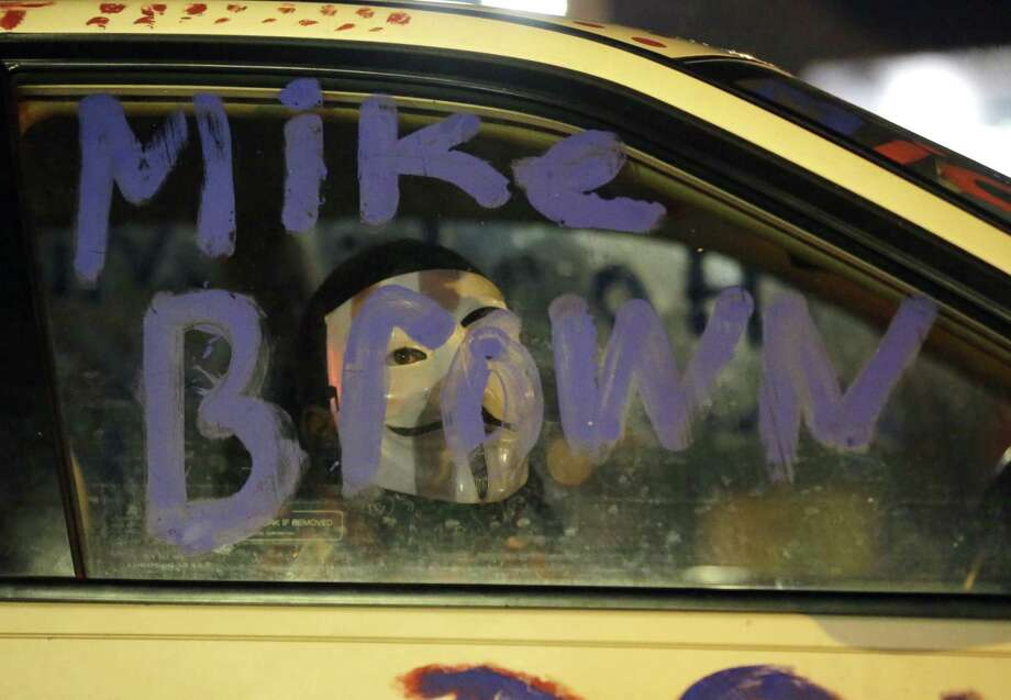 A protester sits in a car looking through the window as the car is parked across from the police department, Monday, Nov. 24, 2014, in Ferguson, Mo., more than three months after an unarmed black 18-year-old man was shot and killed there by a white policeman in Ferguson. Ferguson and the St. Louis region are on edge in anticipation of the announcement by a grand jury whether to criminally charge Officer Darren Wilson in the killing of Michael Brown. Photo: (AP Photo/Charlie Riedel) / AP