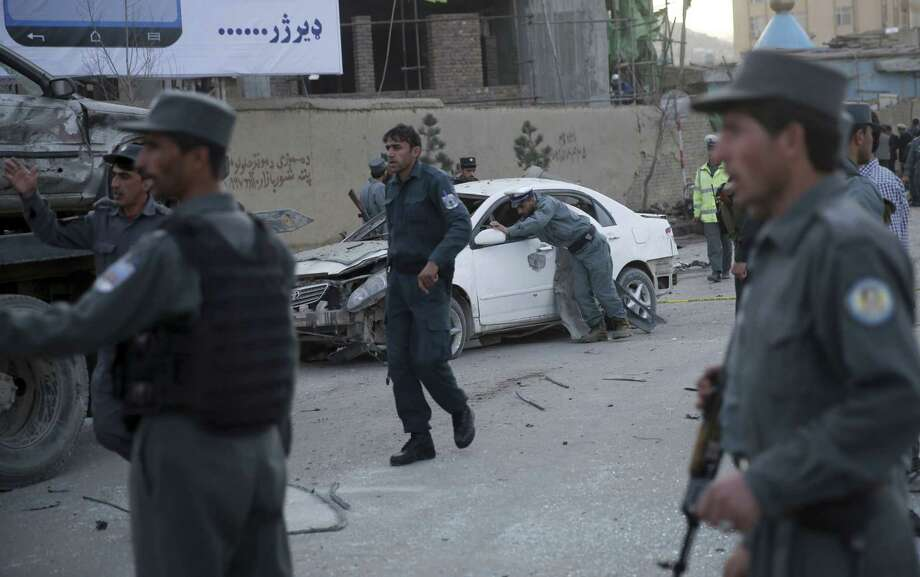 A traffic policeman moves a damaged vehicle at the site of a suicide attack in Kabul, Afghanistan, Wednesday. The suicide car bombing in the heart of the Afghan capital killed several people and wounded tens, according to Afghan security officials. Photo: Massoud Hossaini — The Associated Press  / AP