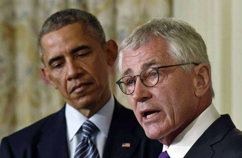 President Barack Obama, left, listens as Defense Secretary Chuck Hagel, right, talks about his resignation during an event in the State Dining Room of the White House in Washington, Monday, Nov. 24, 2014. Photo: (AP Photo/Susan Walsh) / AP