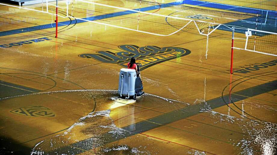 A worker begins the task of cleaning up at least an inch of water covering the playing floor at Pauley Pavilion after a broken 30-inch water main under nearby Sunset Boulevard caused flooding that inundated several areas of the UCLA campus in the Westwood section of Los Angeles on Tuesday. Photo: Mike Meadows — The Associated Press  / FR55673 Ap