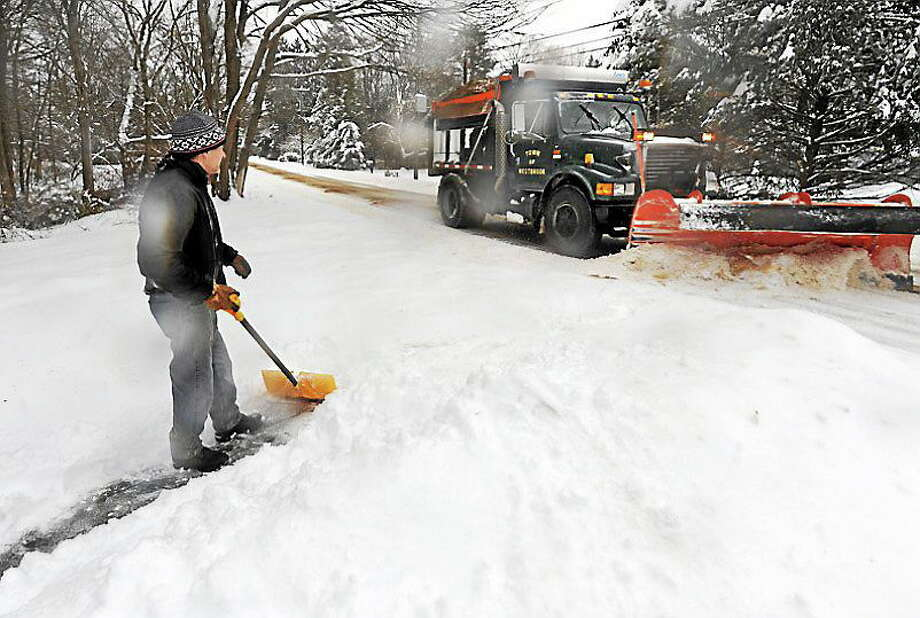 Jack Gambardella shovels out his driveway Feb. 5 as the town of Westbrook's plow goes by. Photo: Mara Lavitt - New Haven Register File Photo