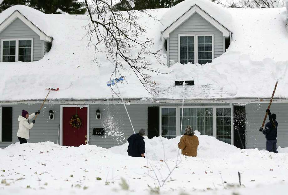 People clear snow from a house on Nov. 22, 2014, in Orchard Park, N.Y. Western New York continues to dig out from the heavy snow dropped by this week by lake-effect snowstorms. Photo: AP Photo/Mike Groll  / AP