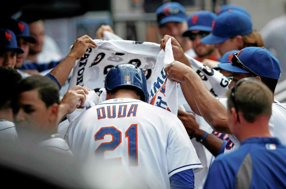 In a routine reserved for home run hitters, Mets teammates drape Lucas Duda with towels after Duda hit an eighth-inning, two-run homer off Philadelphia Phillies reliever Phillippe Aumont in New York's 11-2 win on Wednesday at Citi Field. Photo: Kathy Willens — The Associated Press  / AP
