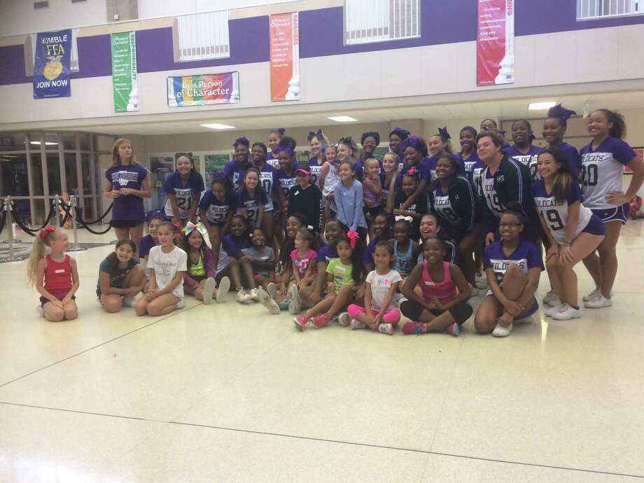 The Humble High School cheerleaders and the Humble Area Football League cheerleaders pose for a picture at the end of a clinic that the high school cheerleaders put on at the school on Saturday, August 12 Photo: Elliott Lapin