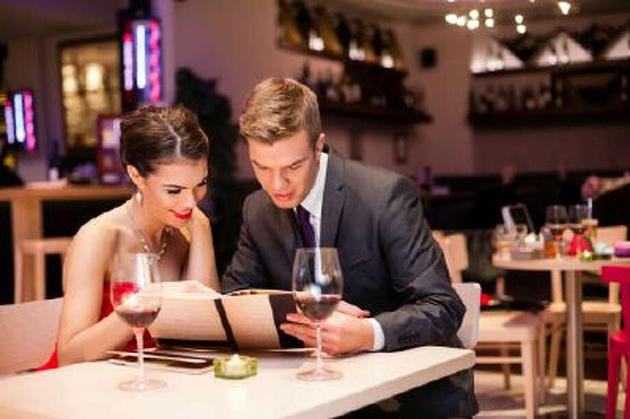 A couple looks at a restaurant menu. Photo: Getty Images/iStockphoto / iStockphoto