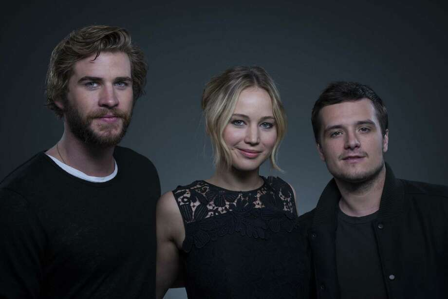 """Co-starring in """"The Hunger Games: Mockingjay - Part 1"""" from left, actors Liam Hemsworth, Jennifer Lawrence and Josh Hutcherson pose for a portrait on Saturday, Nov. 15, 2014 in New York. Photo: Photo By Drew Gurian/Invision/AP  / Invision"""