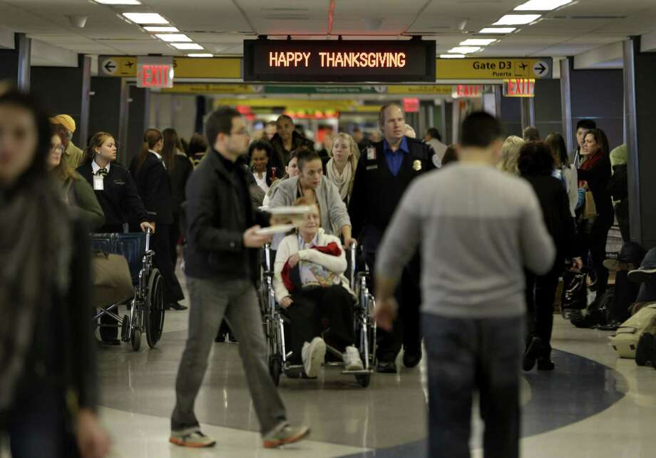 """FILE - In this Nov. 26, 2013, file photo, travelers walk under a sign reading """"Happy Thanksgiving"""" at LaGuardia Airport in New York. There will be 12.3 million roundtrip passengers, globally, on U.S. airlines during the 2014 holiday travel period, up 1.5 percent from 2013, according to the industryís lobbying group, Airlines for America. Photo: (AP Photo/Seth Wenig, File) / AP"""