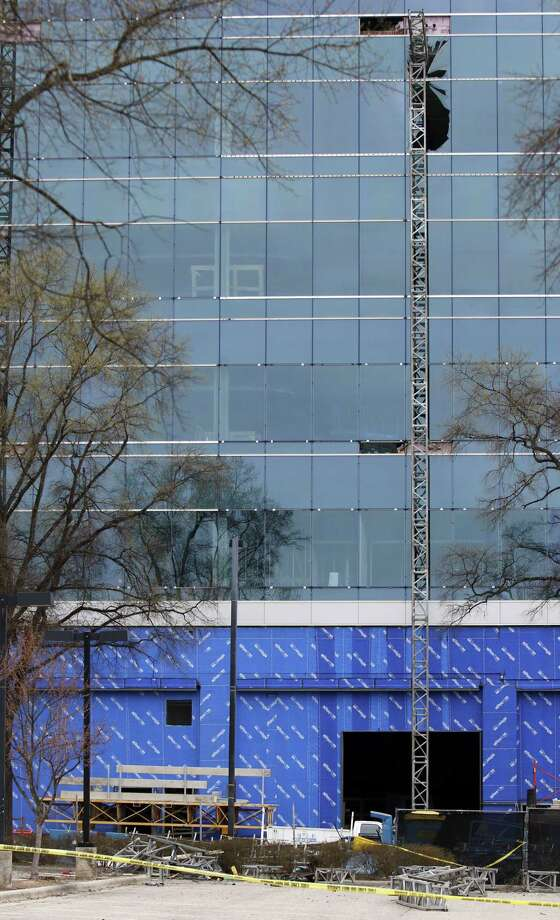 Yellow tape surrounds the piece of scaffolding that fell to the ground as a large section of framework hangs near shattered windows of the Charter Square building at the scene of a construction accident in downtown Raleigh, NC Monday, March 23, 2015.  A scaffolding fell and crashed into the Charter Square project, killing three workers and sending another to a hospital. (AP Photo/The News & Observer, Harry Lynch) Photo: AP / The News & Observer