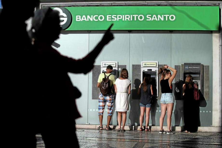 In this July 28, 2014 photo, people use ATMs at a branch of Portuguese bank Banco Espirito Santo in Lisbon. The Espirito Santo family business survived wars, dictatorship, revolution and family feuds for almost 150 years. Now, one of Europe's last banking dynasties is being stripped of its wealth and influence amid accounting irregularities, huge unreported debts, and a police investigation. (AP Photo/Francisco Seco) Photo: AP / AP