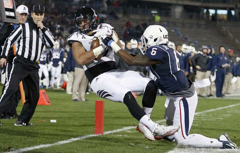 Cincinnati tight end Jake Golic, second from right, comes down with the touchdown reception against UConn cornerback Jhavon Williams (6) during the first half Saturday. Photo: Michael Dwyer — The Associated Press  / AP