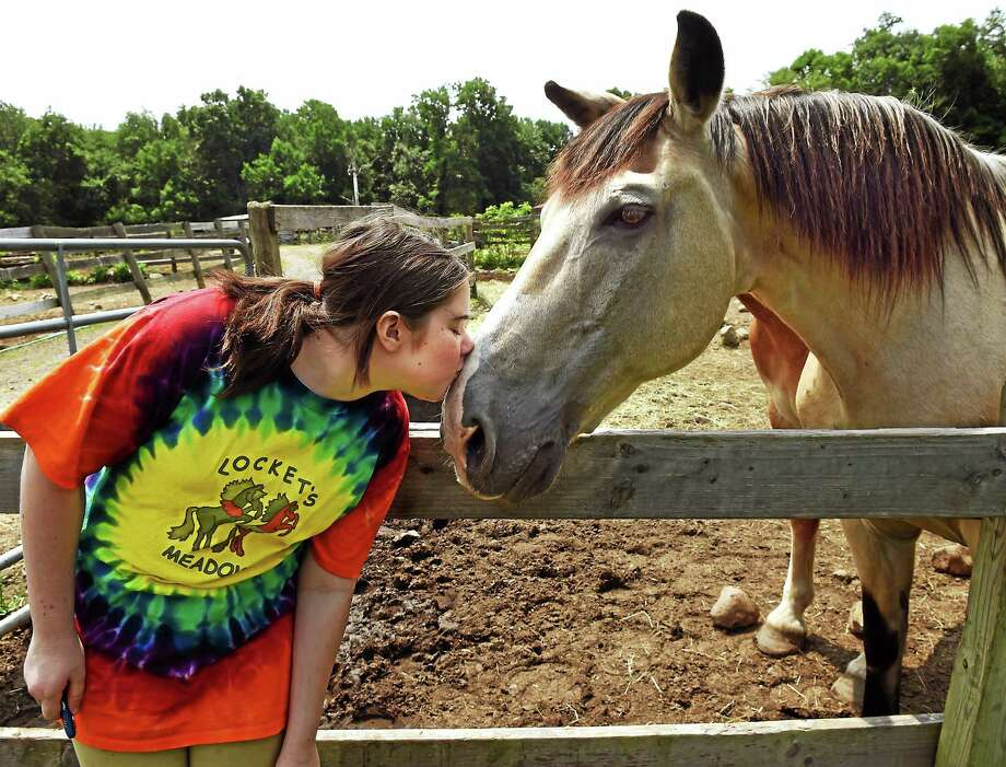 Fiona Hynes, 12, of Woodbridge, a volunteer and rider at Locket's Meadow Farm, gives a smooch to Josh, one of the farm's horses. Photo: Mara Lavitt — New Haven Register   / Mara Lavitt
