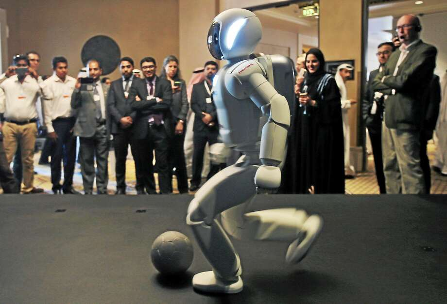 A humanoid robot designed and developed by Honda and named Asimo plays football for the audience at the end of the company's presentation during the last day of the Government Summit in Dubai, United Arab Emirates on Feb. 11, 2015. Photo: AP Photo/Kamran Jebreili  / AP