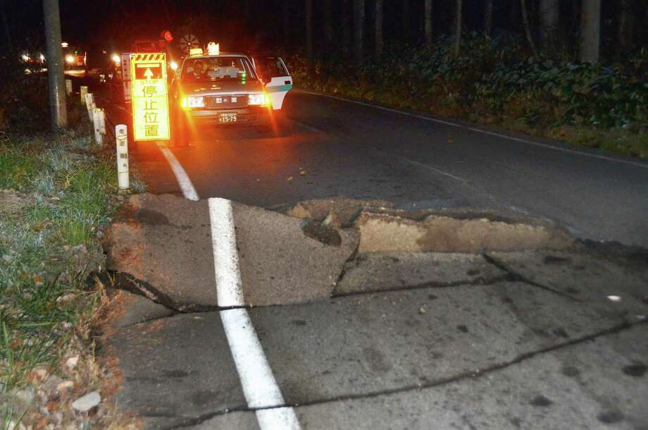 A taxi stops by a crack on the road that leads to Hakuba from Nagano, Nagano Prefecture, after a strong earthquake hit central Japan, Saturday, Nov. 22, 2014. The magnitude-6.8 earthquake struck in the mountainous area of central Japan Saturday night. No tsunami warning was issued. (AP Photo/Kyodo News) JAPAN OUT, CREDIT MANDATORY Photo: AP / Kyodo News