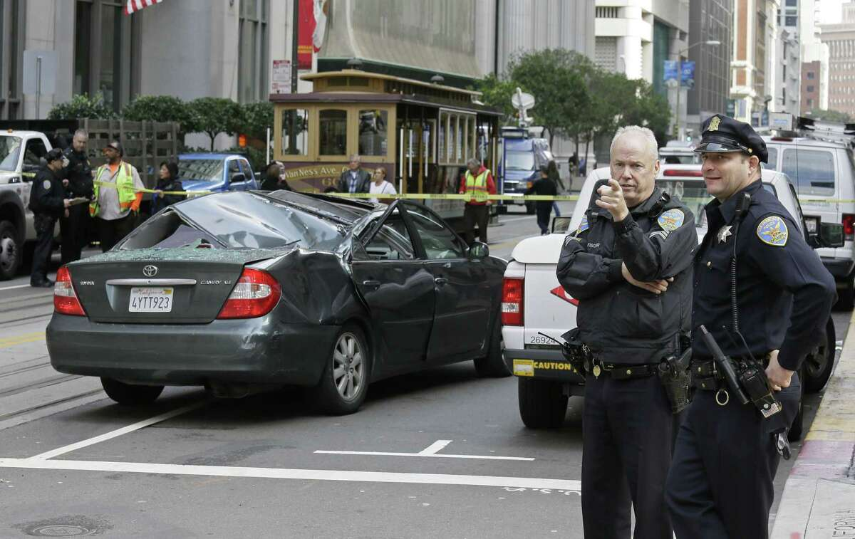 A pair of San Francisco police officers look over the scene where a window washer fell 11 stories onto a moving car Friday, Nov. 21, 2014, in San Francisco. Police said the San Francisco window washer has survived the fall. The man, whose name and age were not immediately available, was transported to a hospital with critical injuries. (AP Photo/Eric Risberg)