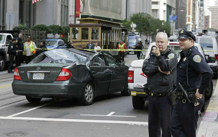 A pair of San Francisco police officers look over the scene where a window washer fell 11 stories onto a moving car Friday, Nov. 21, 2014, in San Francisco. Police said the San Francisco window washer has survived the fall.  The man, whose name and age were not immediately available, was transported to a hospital with critical injuries. (AP Photo/Eric Risberg) Photo: AP / AP