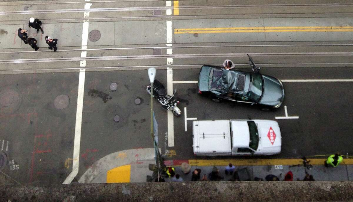 Police look over a car that has a caved in roof after a window washer fell at least 11 stories onto a moving vehicle in San Francisco, Friday, Nov. 21, 2014. (AP Photo/Michael Liedtke)