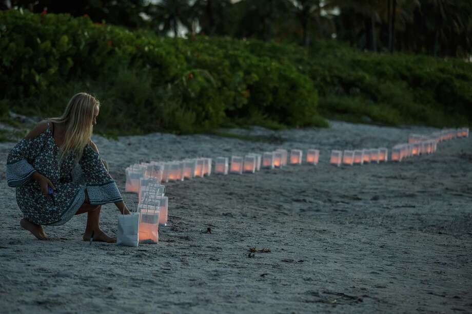 Lilly Folds lights paper lanterns during a candlelight vigil and paper balloon release at Jupiter Inlet Park Monday for teenagers Austin Stephanos and Perry Cohen in Jupiter, Fla. The teens were last seen Friday afternoon buying fuel near Jupiter and were believed to have been heading toward the Bahamas. Photo: Thomas Cordy/The Palm Beach Post Via AP / The Palm Beach Post