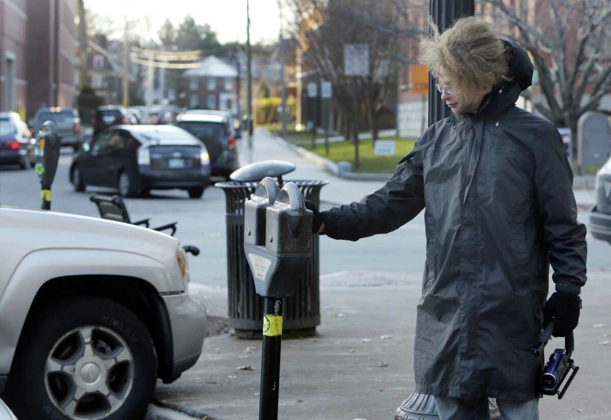 In this photo taken Wednesday Nov. 19, 2014 one of many self-proclaimed ìRobin Hoodersî Garret Ean puts money in expired meters ahead of parking enforcement officers on Main St. in Keene, N.H. A merry band of Keene activists stalk parking enforcement officers, pumping quarters into expired meters before the officers write tickets. But city officials say their practice of taunting and videotaping the officers interferes with their work and stresses them out. The New Hampshire Supreme Court is deliberating if there is a line to be drawn between constitutionally-protected free speech rights and protecting government employees from harassment. (AP Photo/Jim Cole)
