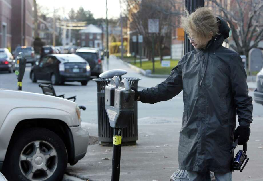 In this photo taken Wednesday Nov. 19, 2014 one of many self-proclaimed ìRobin Hoodersî Garret Ean puts money in expired meters ahead of parking enforcement officers on Main St. in Keene, N.H. A merry band of Keene activists stalk  parking enforcement officers, pumping quarters into expired meters before the officers write tickets. But city officials say their practice of taunting and videotaping the officers interferes with their work and stresses them out. The New Hampshire Supreme Court is deliberating if there is a line to be drawn between constitutionally-protected free speech rights and protecting government employees from harassment. (AP Photo/Jim Cole) Photo: AP / AP