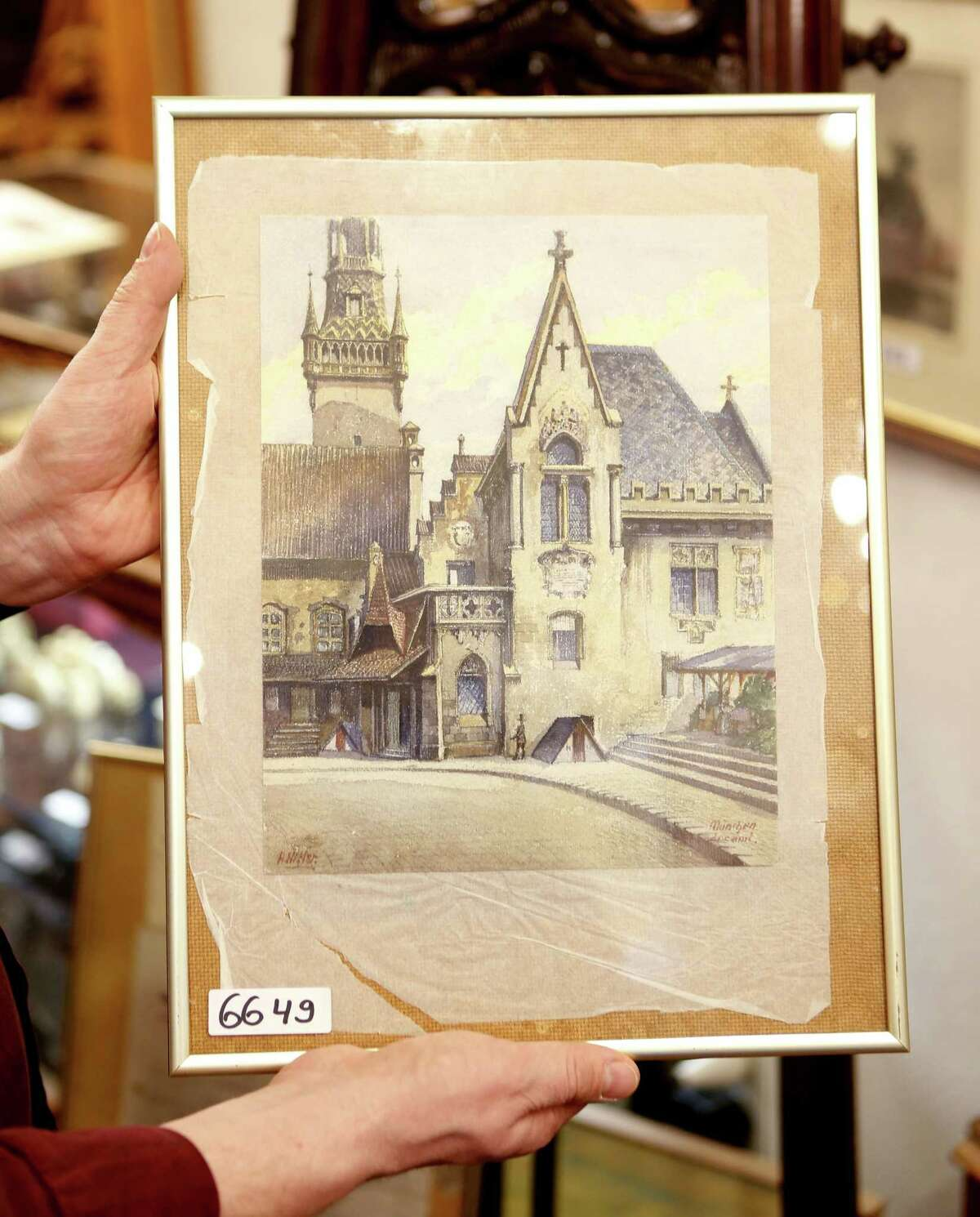 In this photo taken Wednesday, Nov. 19, 2014, a picture titled ìThe Old City Hallî that - as the auction house said - was painted by Adolf Hitler is displayed in an auction house in Nuremberg, Germany. The 100-year-old watercolor of Munichís city hall is expected to fetch at least 50,000 euros (US$ 60,000) at auction this weekend, not so much for its artistic value as for the signature in the bottom left corner: A. Hitler. (AP Photo/Michael Probst)