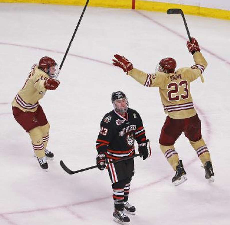 Boston College's Patrick Brown celebrates the go-ahead goal and eventual game-winner with Ryan Fitzgerald in the third period as Northeastern's Colton Saucerman reacts in the Beanpot finals at TD Garden Monday.