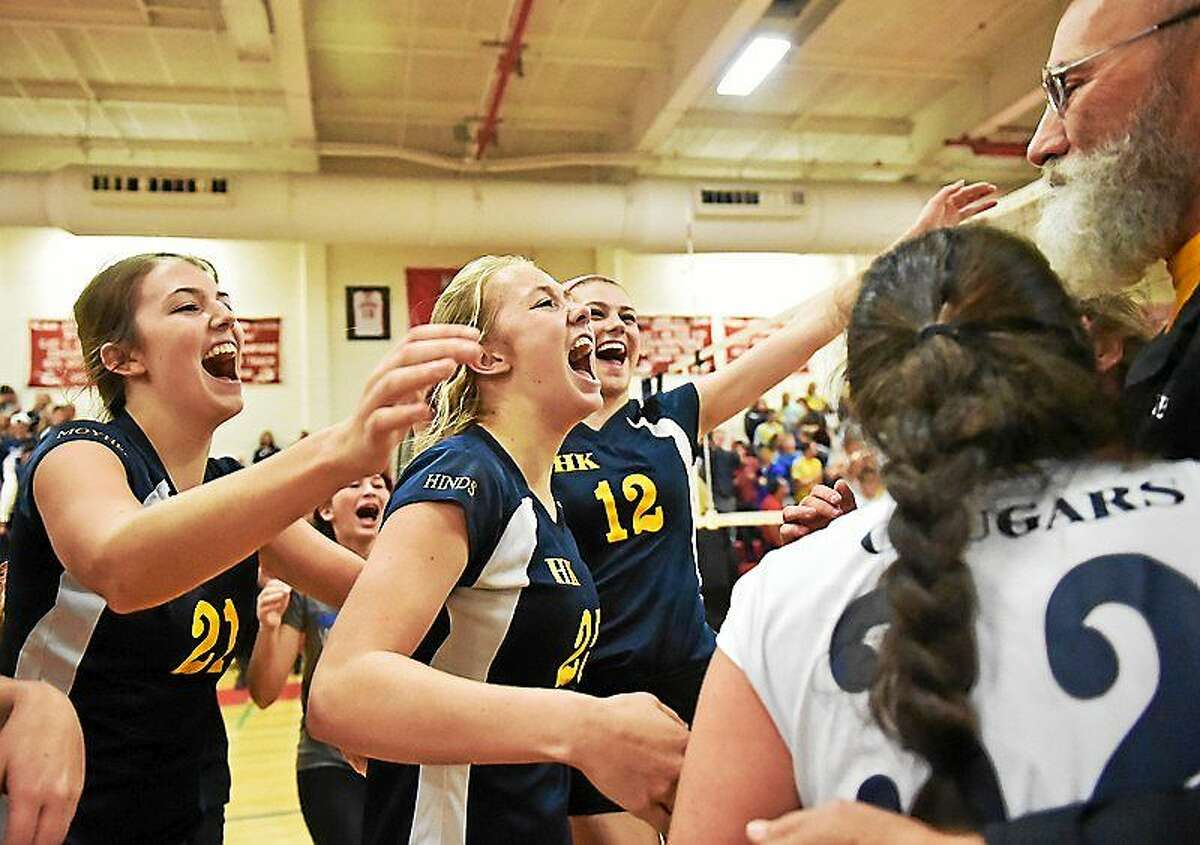 H-K players, from left, Carley Moyher, Mackenzie Hinds, and Lauren Brough celebrate with coach Rich Langer after the Cougars defeated Morgan in the Shoreline Conference championship game at Wilbur Cross High School.