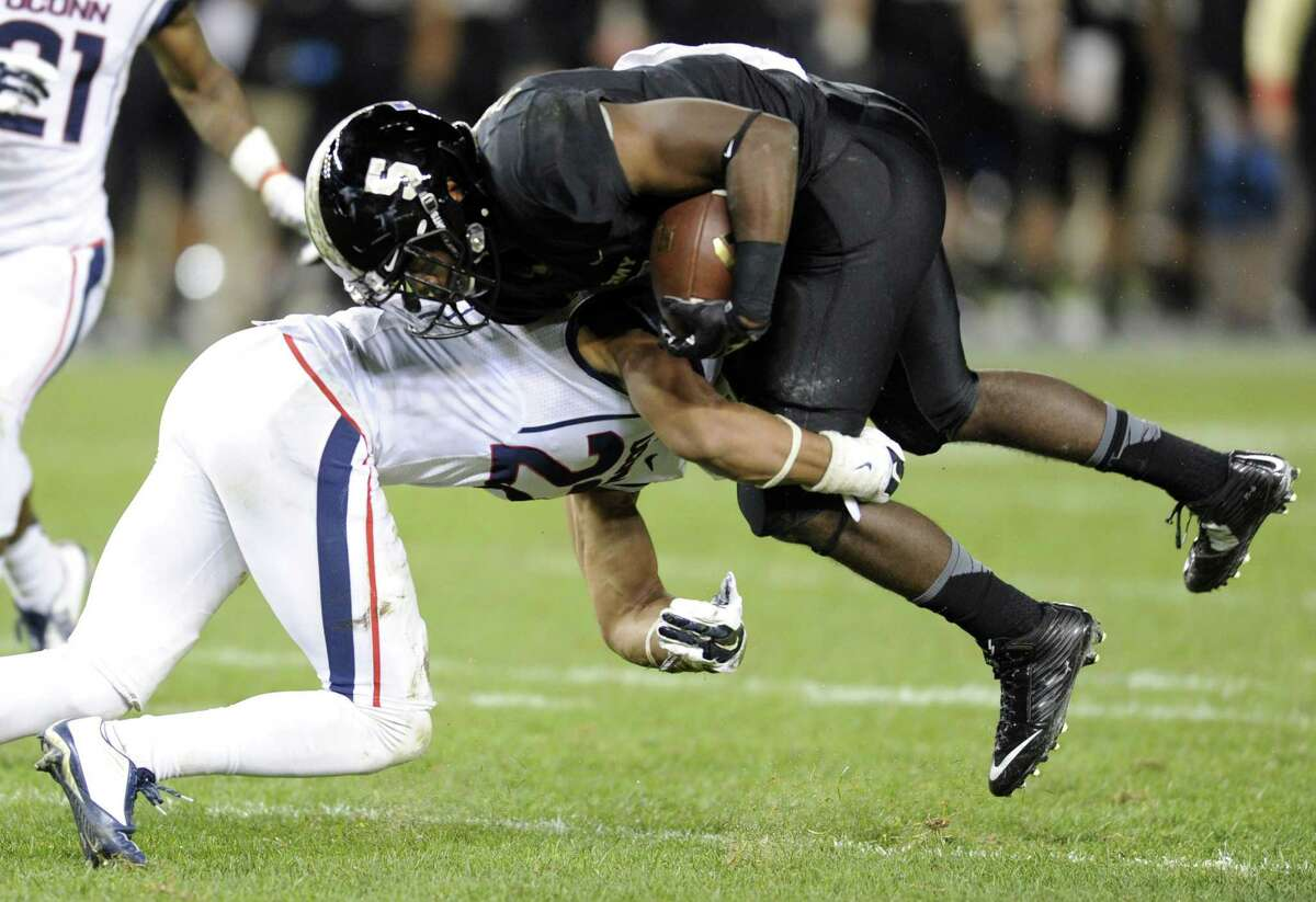 Army running back Joe Walker is tackled by UConn safety Andrew Adams during a Nov. 8 game at Yankee Stadium.