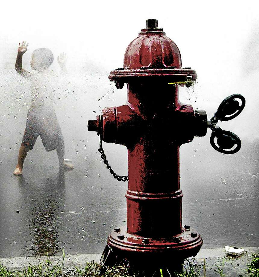 Hayd'n Santiago keeps cool running around the fire hydrant on Portland Street in Middletown. Photo: File