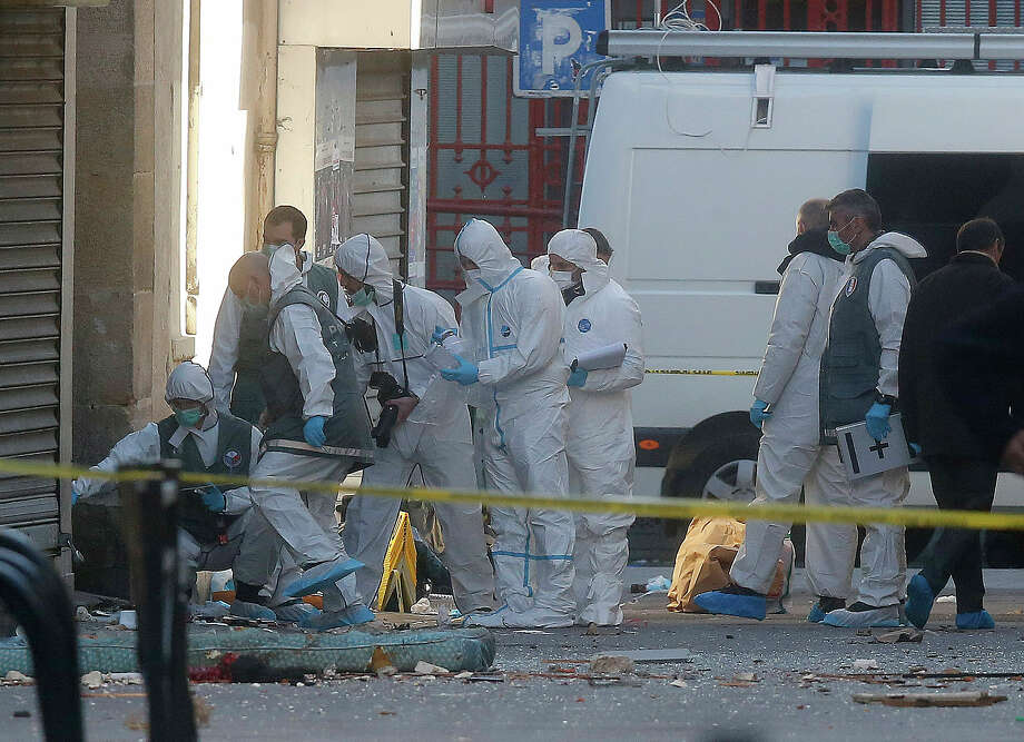 Forensic experts examine the scene in Saint-Denis, near Paris on Nov. 18, 2015. A woman wearing an explosive suicide vest blew herself up Wednesday as heavily armed police tried to storm a suburban Paris apartment where the suspected mastermind of last week's attacks was believed to be holed up, police said. Photo: AP Photo/Michel Euler  / AP