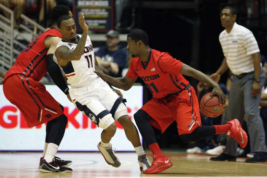 Dayton guard Scoochie Smith, right, dribbles past UConn guard Ryan Boatright during Friday's game in San Juan, Puerto Rico. Photo: Ricardo Arduengo — The Associated Press  / AP