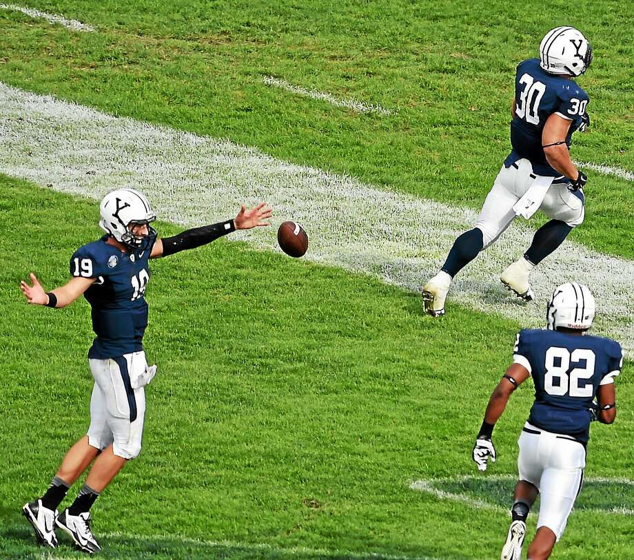 Yale quarterback Morgan Roberts, left, celebrates with teammate Tyler Varga, center, after he scored a touchdown against Lehigh during a Sept. 20 game at Yale Bowl. Photo: Peter Hvizdak — Register File Photo  / ©2014 Peter Hvizdak