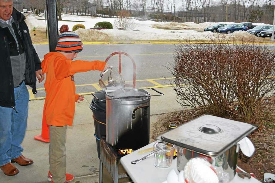 Van Buren Moody Elementary School fourth-grader Eric Wilson pours sap into a bucket as it begins to boil into maple syrup. Photo: Brian Zahn — The Middletown Press