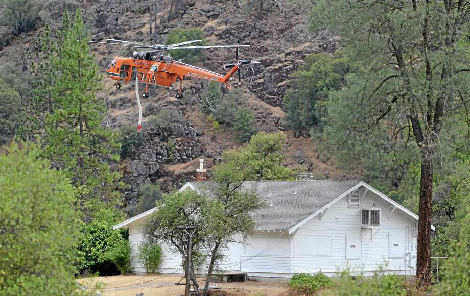 A helicopter hovers above a home as it prepares to dip water from the nearby Merced River in El Portal, Calif.,  on Monday,  July 28, 2014.(AP Photo/The Fresno Bee, Mark Crosse) LOCAL PRINT OUT (VISALIA TIMES-DELTA, REEDY EXPONENT, KINGBURG RECORDER, SELMA ENTERPRISE, HANFORD SENTINEL, PORTERVILLE RECORDER, MADERA TRIBUNE, THE BUSINESS JOURANL FRENSO); LOCAL TELEVISION OUT (KSEE24, KFSN30, KGE47, KMPH26) Photo: AP / ap