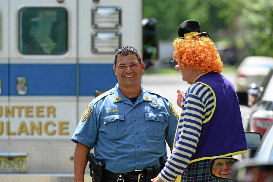 """Westwood Police Officer Niko Pieratos talks with Jack """"Poppi T Clown"""" Erbstein at the accident site in  Westwood, N.J., Monday, July 28, 2014. Westwood Police responded to the scene of a Toyota sedan striking a utility pole on Berkeley Ave Monday just before noon. According to Jack """"Poppi T Clown"""" Erbstein, of Mahwah, who witnessed the accident said that the driver was reaching for a GPS device that fell off the windshield when she veered off the road and into the pole after a show at the day camp at Berkeley Elementary School. The driver was part of Call Us Clowns, a not-for-profit caring organization that puts on clown shows at schools and hospitals. Police Chief Frank Regino says the 68-yerar-old sustained minor injuries.  (AP Photo/Northjersey.com, Tariq Zahawi) ONLINE OUT; MAGS OUT; TV OUT; INTERNET OUT;  NO ARCHIVING; MANDATORY CREDIT Photo: AP / Northjersey.com"""