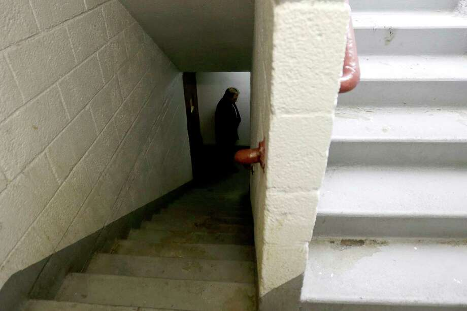 A man who identified himself as a detective with the district attorney's office inspects the area in a stairwell where a man was allegedly shot by a police officer the night before at the Louis Pink Houses public housing complex, Friday, Nov. 21, 2014, in Brooklyn borough of New York.  A rookie police officer with his gun drawn shot to death 28-year-old Akai Gurley, an unarmed, innocent man in the darkened stairwell of the crime-ridden public housing complex, New York City police officials said Friday.  The shooting appeared to be an accident, Police Commissioner William Bratton said at a news conference.  (AP Photo/Julio Cortez) Photo: AP / AP