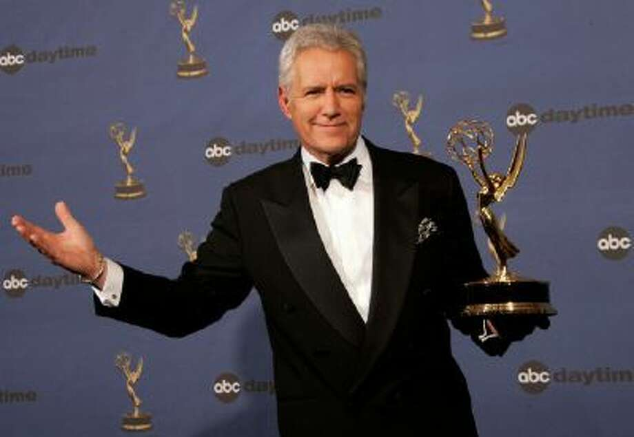 """Alex Trebek holds the award for outstanding game show host, for his work on """"Jeopardy!"""" at the 33rd Annual Daytime Emmy Awards in Los Angeles."""