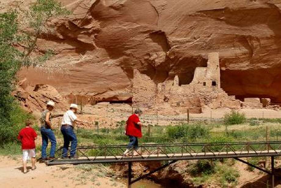 Tourists walk along a bridge in front of ruins inside Canyon de Chelly National Monument, near Chinle, Ariz.