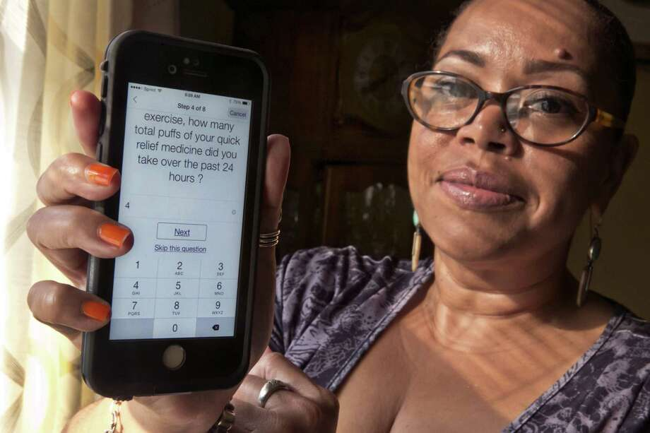 In this July 2, 2015 photo, asthma sufferer Elizabeth Ortiz, who uses the Asthma Health smartphone app daily to track her condition, poses for photos at her apartment, on New York's Lower East Side. Ortiz measures her lung power each day by breathing into an inexpensive plastic device and then typing the results into the app, which also asks if sheís had difficulty breathing or sleeping, or taken medication that day. Photo: AP Photo/Richard Drew  / AP
