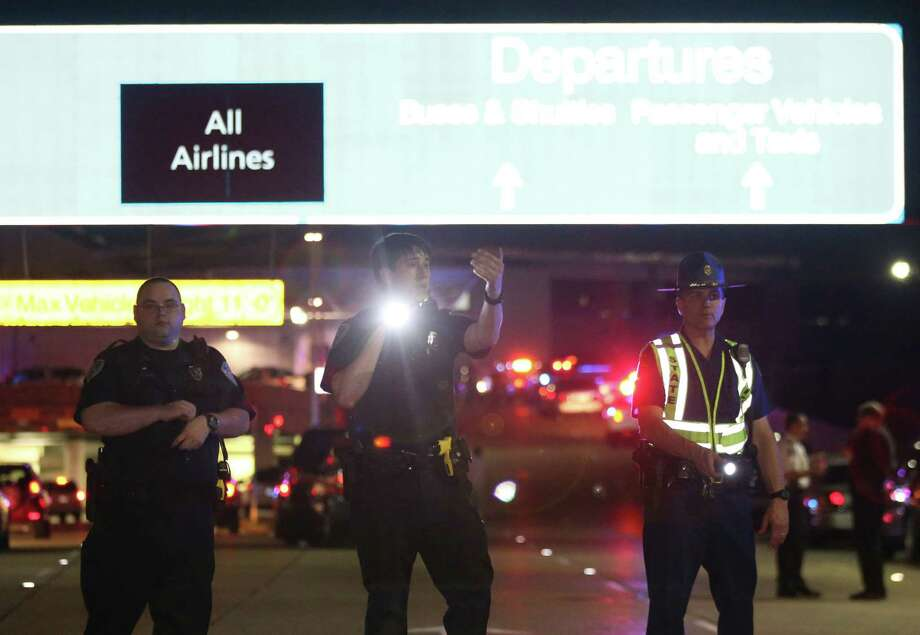 Officers stand at the entrance to New Orleans International Airport, Friday, March 20, 2015, in Kenner, La. Richard White sprayed a TSA agent in the face with wasp killer then slashed a second guard with a machete before a third agent shot him three times at a security checkpoint in the New Orleans international airport Friday. (AP Photos/Jonathan Bachman) Photo: AP / FR170615 AP