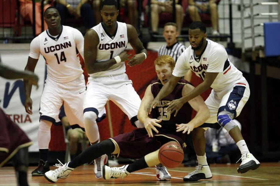 College of Charleston center David Wishom battles for a loose ball against UConn's Sam Cassell Jr., right, during the Huskies' 65-57 win on Thursday afternoon at the Puerto Rico Tip-Off tournament in San Juan. At left is Rakim Lubin (14) and Phil Nolan (1). Photo: Ricardo Arduengo — The Associated Press  / AP