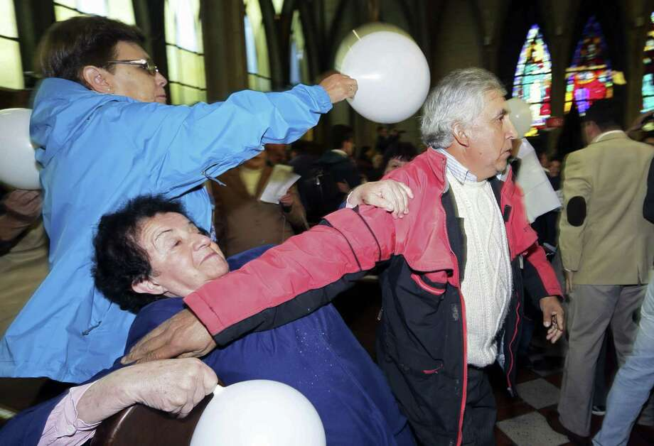 A supporter of Rev. Juan Barros, right, tries to restrain protestors as Barros, not seen,  enters the cathedral for his ordination ceremony as bishop in Osorno, Chile, Saturday, March 21, 2015.  Barros was ordained amid protests of people that accuse him of covering up sexual abuse committed by his mentor  Rev. Fernando Karadima in the 1980s and '90s.(AP Photo/Mario Mendoza Cabrera) -  CHILE OUT - NO USAR EN CHILE Photo: AP / AP