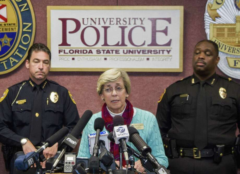 Mary Coburn, vice president of student affairs, center, talks to the media during a news conference about a shooting at the Strozier Library on the Florida State University campus, Thursday, Nov. 20, 2014, in Tallahassee, Fla. Three students were wounded and the gunman was shot and killed by police officers. Tallahassee police Chief Michael Deleo, left, and FSU police Chief David Perry stand in the background. (AP Photo/Mark Wallheiser) Photo: AP / FR171224 AP