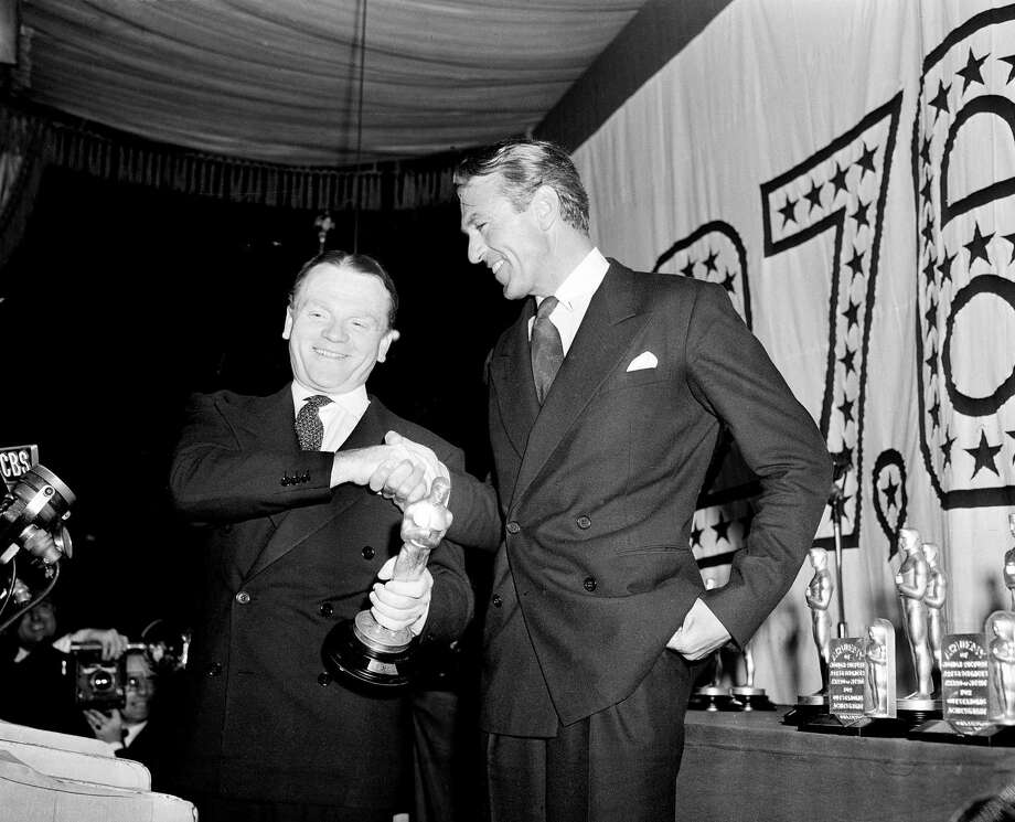 """FILE-In this March 4, 1943 file photo, actor Jimmy Cagney, left, is congratulated by Gary Cooper after receiving the best actor Oscar statuette for his role in """"Yankee Doodle Dandy"""" at the 1942 Academy Awards banquet at Cocoanut Grove, Ambassador Hotel, in Los Angeles. The auctioneer Nate D. Sanders will sell Cagney's Oscar statuette to the highest bidder on November 20, 2014.  (AP Photo/John T. Burns, File) Photo: AP / AP"""