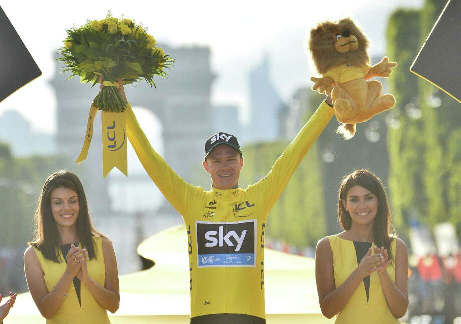 Britain's Chris Froome celebrates as he stands on the podium after winning the Tour de France on Sunday. Photo: The Associated Press  / L'Equipe