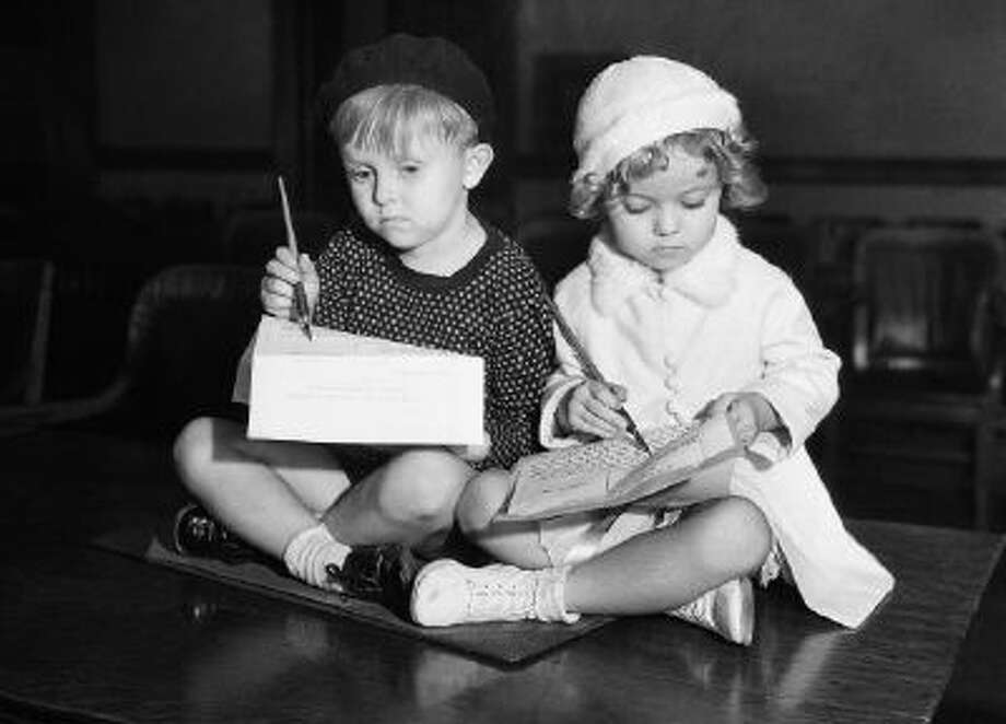 Flaming youth will be depicted on the screen in the from of these two tots, whose respective parents have signed contracts for them to appear in a series of baby shorts on October 10, 1932. They are Georgie Smith and Shirley Temple, and photo shows 'em signing on the dotted line, just as their parents did - at least they're scratching with gusto.