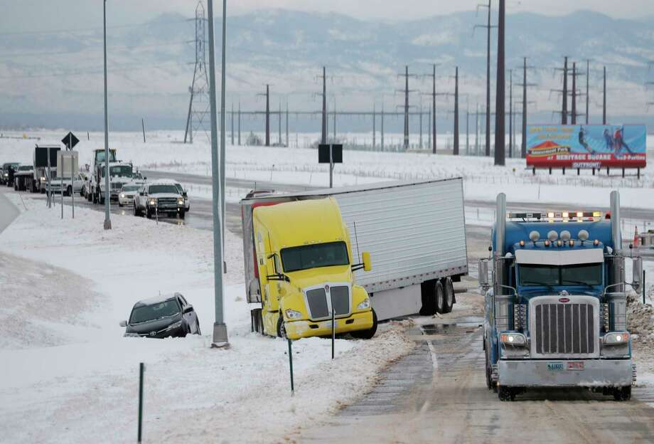 A tow truck, right, pulls up to clear a tractor-trailer and sports utility vehicle stuck in snow on an off ramp off Interstate 70 as a winter storm packing high winds and snow blankets the plains Tuesday, Nov. 17, 2015, in Aurora, Colo. The storm has closed much of Interstate 70, Colorado's main east-west highway, because of blizzard conditions on the Eastern Plains as well as in northwest Kansas. (AP Photo/David Zalubowski) Photo: AP / AP