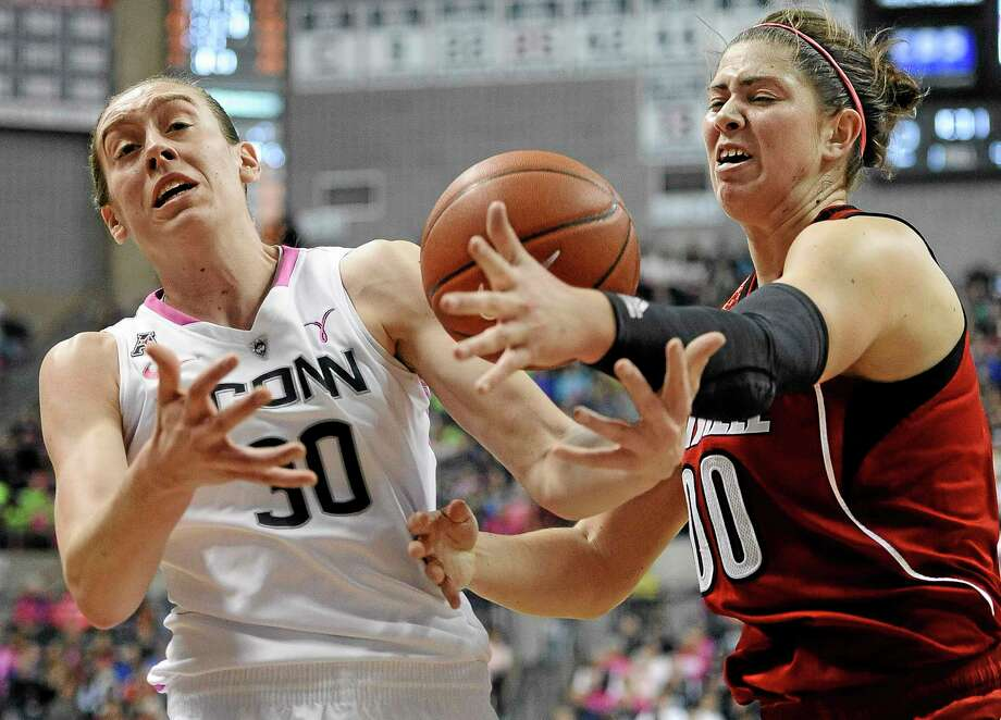 UConn's Breanna Stewart, left, and Louisville's Sara Hammond, right, reach for a loose ball during the first half Sunday's game in Storrs. Photo: Jessica Hill — The Associated Press  / FR125654 AP