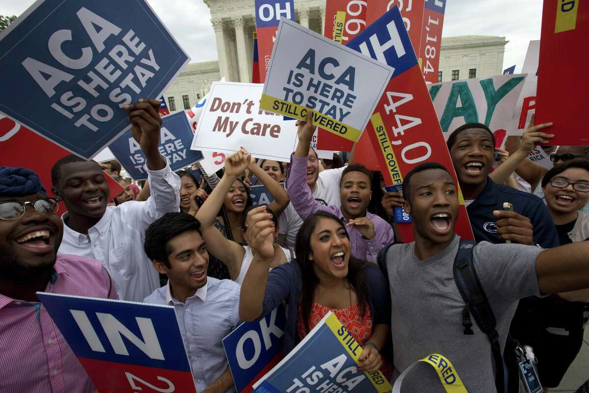 In this June 25, 2015 photo, students cheer as they hold up signs supporting the Affordable Care Act (ACA) after the Supreme Court decided that the ACA may provide nationwide tax subsidies, outside of the Supreme Court in Washington.