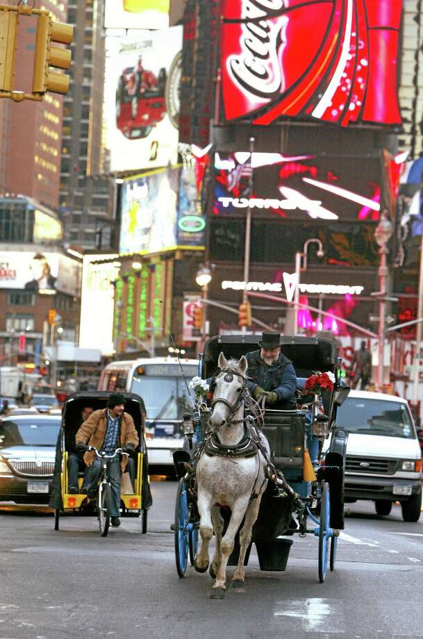 FILE- In this March 1, 2006, file photo, a pedicab driver, left, and a horse-drawn carriage make their way down Broadway in New York's Times Square. New York City Mayor Bill de Blasio seeks to shut down the cityís horse-drawn-carriage industry, believing that it was less than humane to put horses on busy New York City streets. Carriage-horse drivers counter that their industry provides homes for surplus horses from farms and the racing industry that would otherwise be shipped off to slaughterhouses. (AP Photo/Mary Altaffer, File) Photo: AP / AP